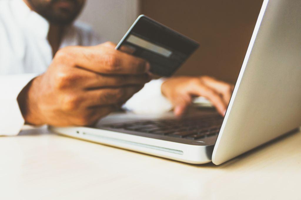 Homem segurando um cartão de crédito que requer bastante cuidado na Black Friday.